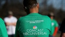 "A Comcast Cares Day volunteer wears a shirt that reads ""Looking forward to giving back, Comcast NBCUniversal""."