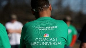 """A Comcast Cares Day volunteer wears a shirt that reads """"Looking forward to giving back, Comcast NBCUniversal""""."""